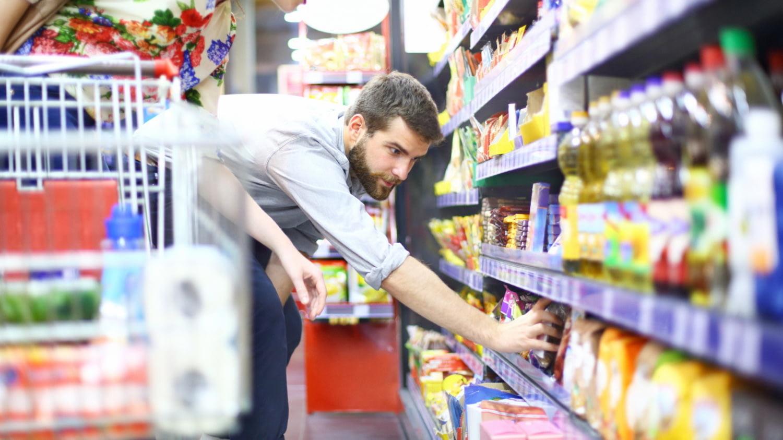 Mann im Supermarkt bückt sich, um ein Produkt aus dem unteren Regal zu nehmen.