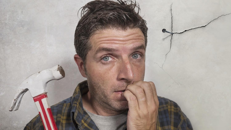 Ein Mann steht verlegen vor einer rissigen Wand, in die er gerade mit einem Hammer einen Nagel eingeschlagen hat