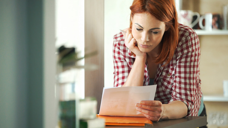 Eine junge Frau liest die überteuerte Rechnung eines Schlüsseldienstes