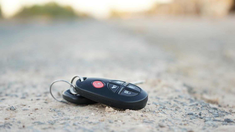 Ein Autoschlüssel liegt auf einer Fahrbahn