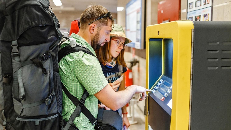 Junges Paar mit Rucksäcken hebt an einem Automaten Geld mit der Kreditkarte ab.