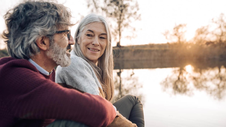 Ein älteres Paar sitzt lächelnd am Ufer eines Sees