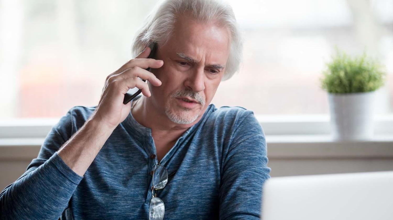 Ein älterer Mann spricht am Smartphone und schaut verärgert