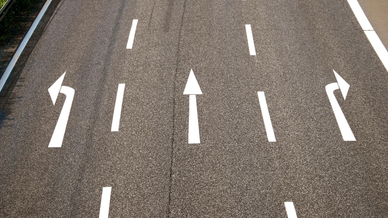 Drei Richtungspfeile auf einer asphaltierten Fahrbahn stehen für die Wahlmöglichkeiten der 3-Wege-Finanzierung