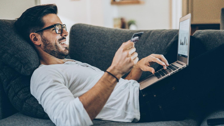Junger Mann liegt auf dem Sofa und kauft mit der Kreditkarte etwas mithilfe des Laptops auf seinem Schoß