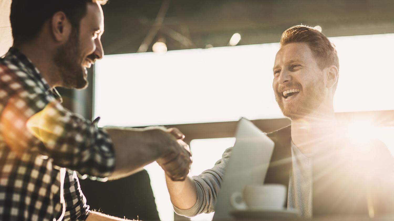 Zwei junge Männer reichen sich nach einem Vertragsabschluss lächelnd die Hände.