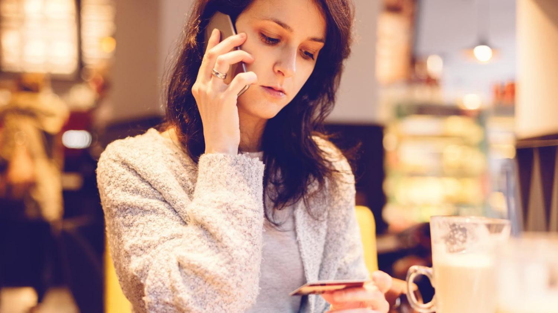 Junge Frau telefoniert und hält dabei ihre Kreditkarte in einer Hand