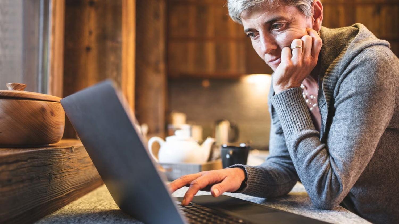 Eine Frau betrachtet in ihrer Küche skeptisch den Bildschirminhalt ihres Laptops