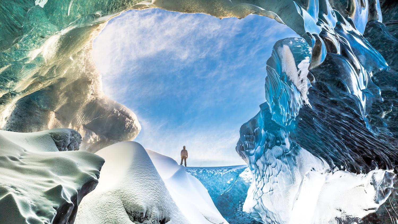 Person steht vor dem Eingang einer riesigen Gletscherhöhle