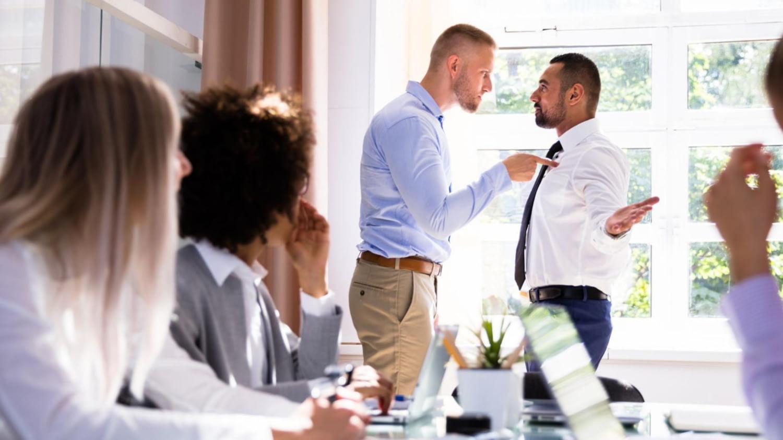 Treffen von mehreren Menschen; zwei Männer davon streiten sich