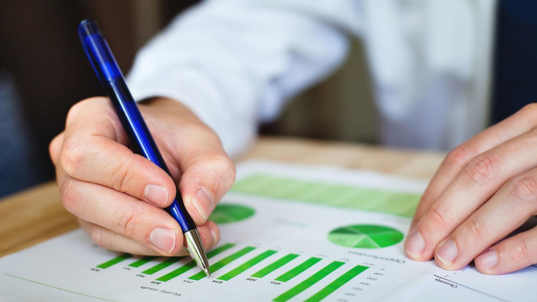 Ein Mann zeigt mit einem Kugelschreiber auf ein Diagramm mit grünen Balken