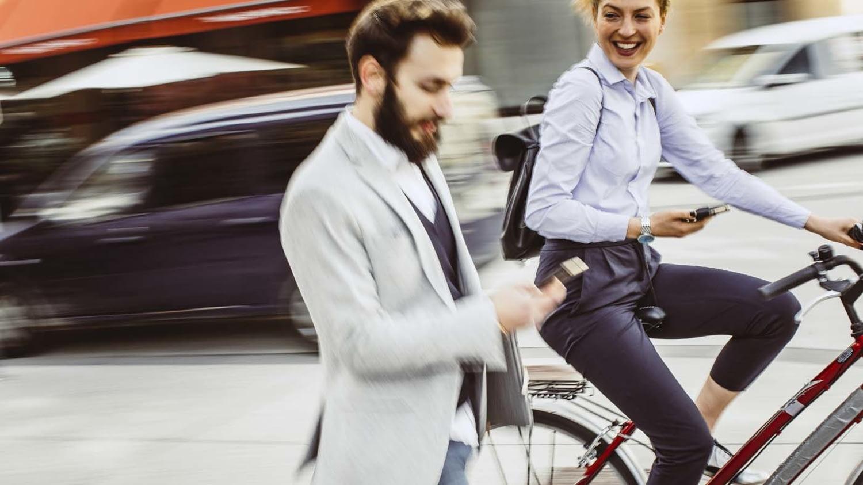 Fahrradfahrerin überholt Fußgänger im Businessoutfit