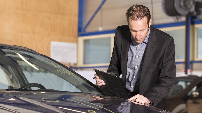 Ein Gutachter untersucht eine Motorhaube auf Schäden