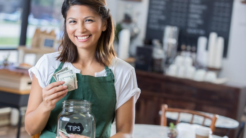 Eine Kellnerin steckt ihr Trinkgeld in ein Sammelglas