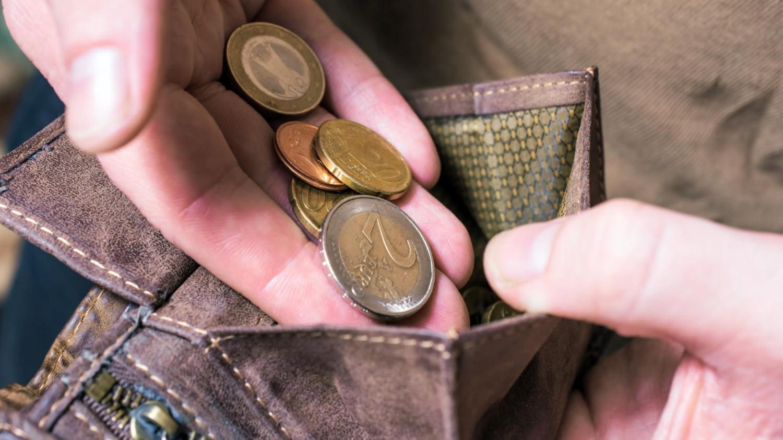 Männliche Hand lässt Münzen in ein Portemonnaie fallen
