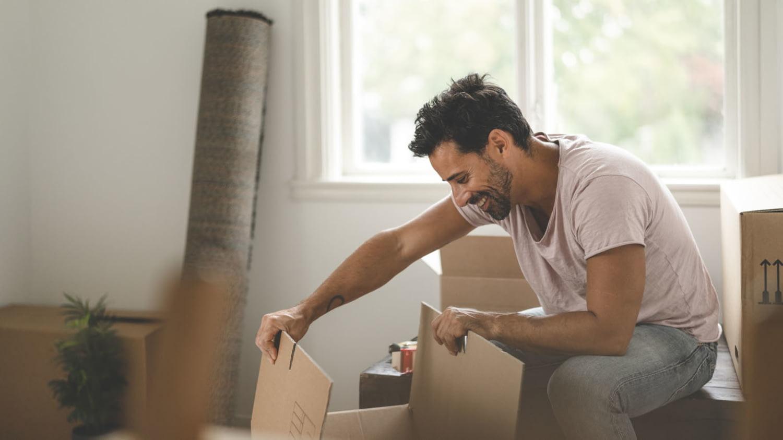 Ein Mann in Jeans und T-Shirt schaut in seiner neuen Wohnung lächelnd in einen Umzugskarton