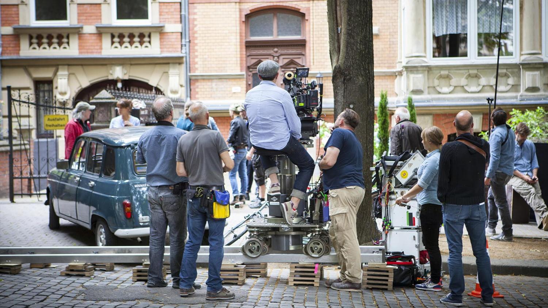Eine Filmcrew dreht eine Szene mit Komparsen in einer Stadt