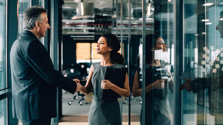 Junge Frau im Kostüm mit Klemmbrett schüttelt einem älteren Herrn im Business-Anzug die Hand.