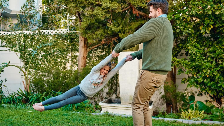 Mann wirbelt seine Tochter im eigenen Garten durch die Luft