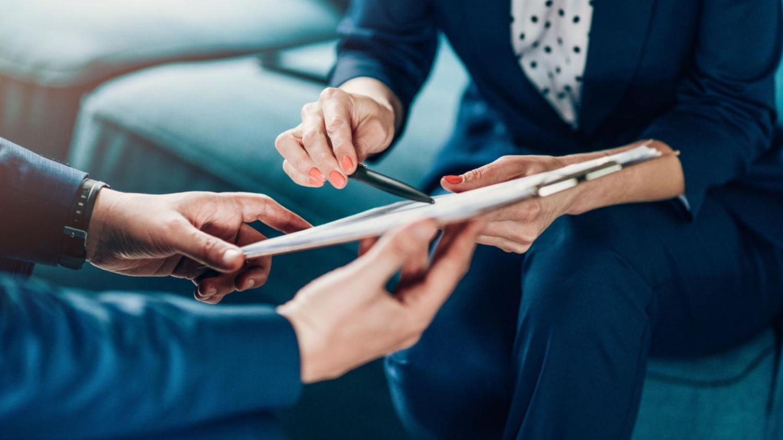 Finanzberaterin erklärt einem Kunden die Unterlagen zu einem Anlageprodukt