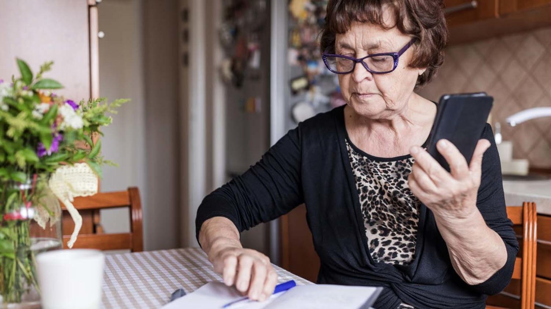 Eine ältere Frau sitzt am Küchentisch und schaut auf ein Notizbuch, während sie ihr Handy in der Hand hält