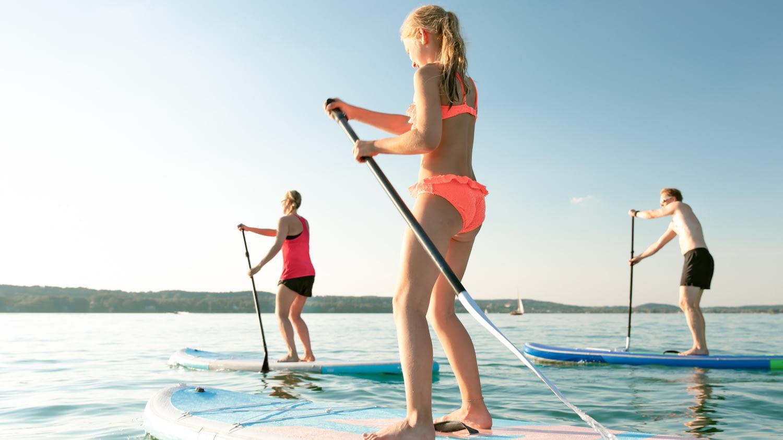 Drei Frauen stehen auf einem Paddel und stoßen sich im Wasser ab.