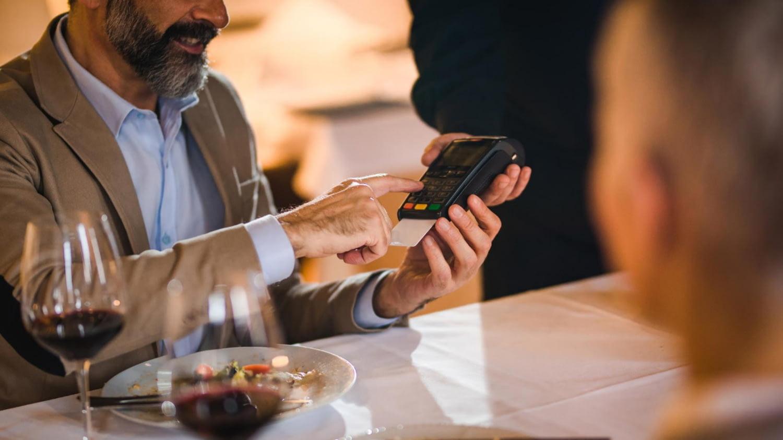 Mann bezahlt in einem Restaurant mit Kreditkarte und gibt dazu seine PIN ein