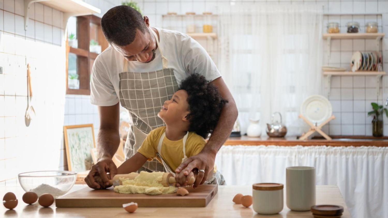 Vater und Kind rollen gemeinsam einen Teig aus