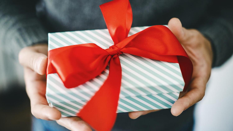 Mann überreicht Geschenkbox mit roter Schleife