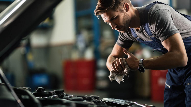 Junger Automechaniker wischt sich die Hände nach der Motorreparatur ab.