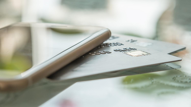 Smartphone und Kreditkarte auf einem Glastisch