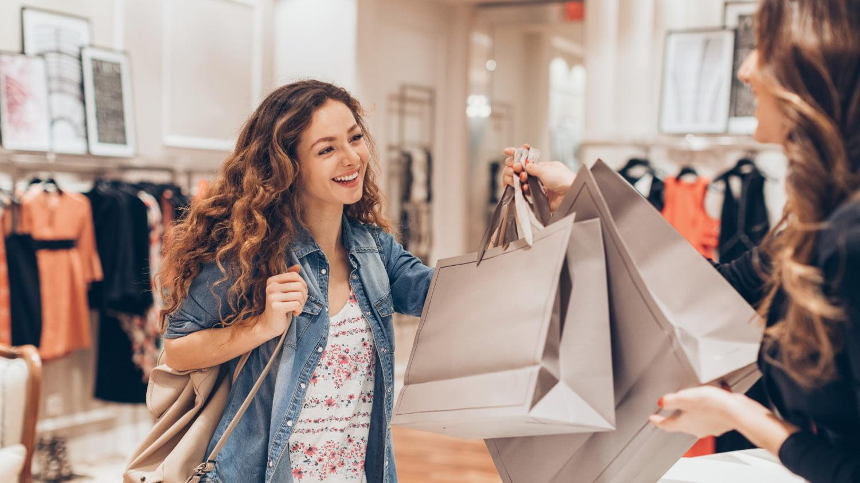 Eine junge Frau nimmt zwei Taschen mit Einkäufen an der Kasse einer Boutique entgegen