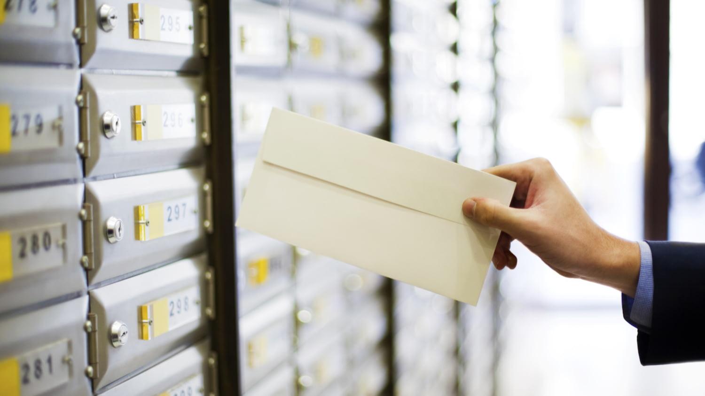 Ein Postbote steckt einen Brief in einen von vielen Briefkästen.