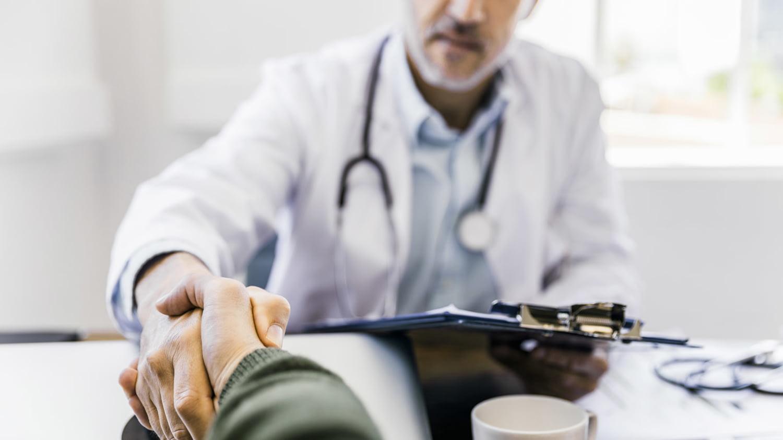 Arzt am Schreibtisch begrüßt einen Patienten mit Handschlag