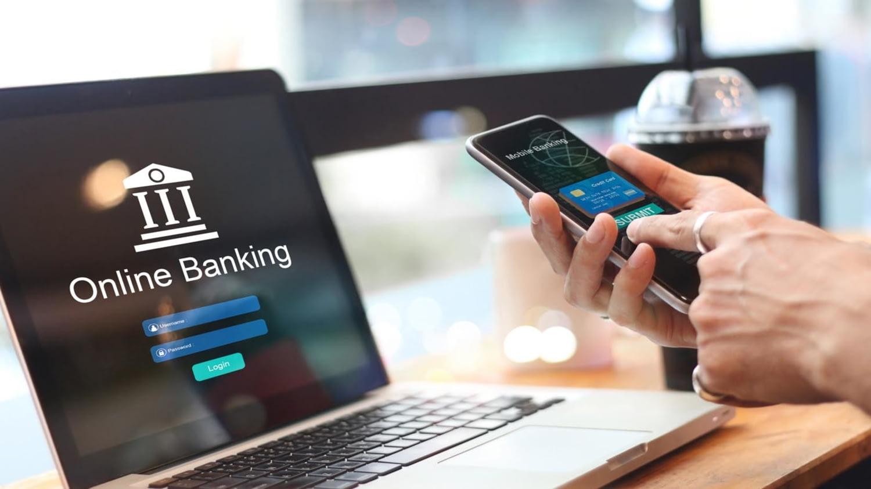 Ein Laptop mit der Aufschrift Online-Banking und Hände, die auf einem Smartphone auf Mobile Banking tippen