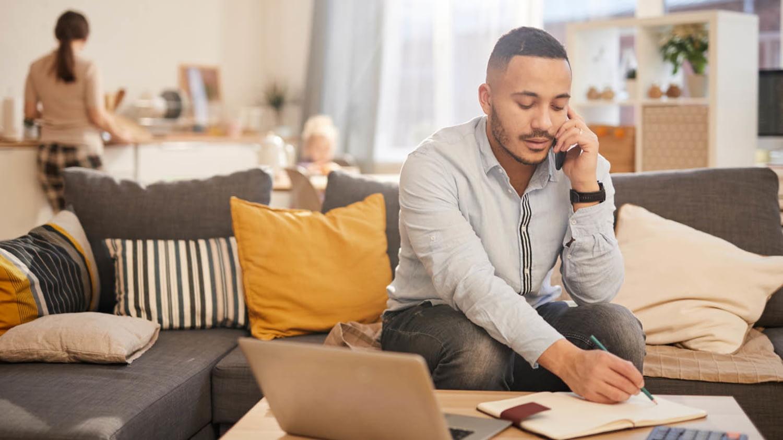 Ein Mann sitzt in seinem Wohnzimmer und macht sich handschriftlich Notizen, während er telefoniert