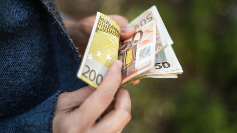 Person zählt Geldbetrag in größeren Euro-Banknoten.