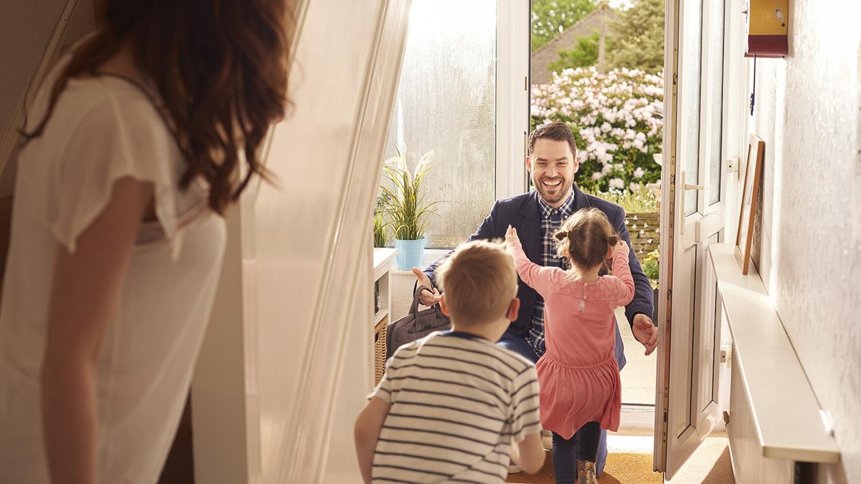 Ein Vater kommt nach Hause und begrüßt seine heranstürmenden Kinder