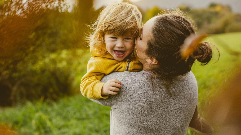 Eine Frau hat ihr lachendes Kind im Arm