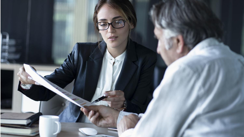 Eine Filialmitarbeiterin erklärt einem Kunden ein Dokument