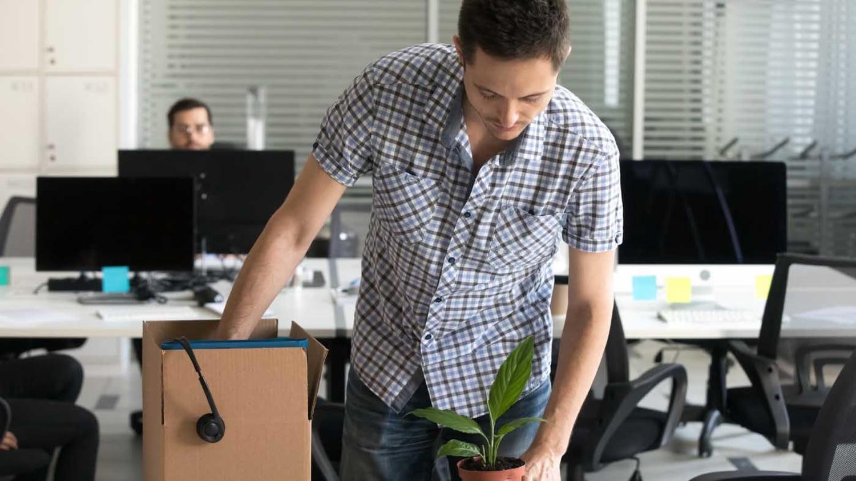 Eine junger Mann packt seine Sachen aus dem Büro in einen Karton