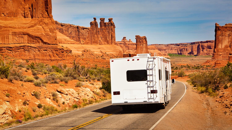 Ein Wohnmobil unterwegs vor beeindruckender Felskulisse im Südwesten der USA