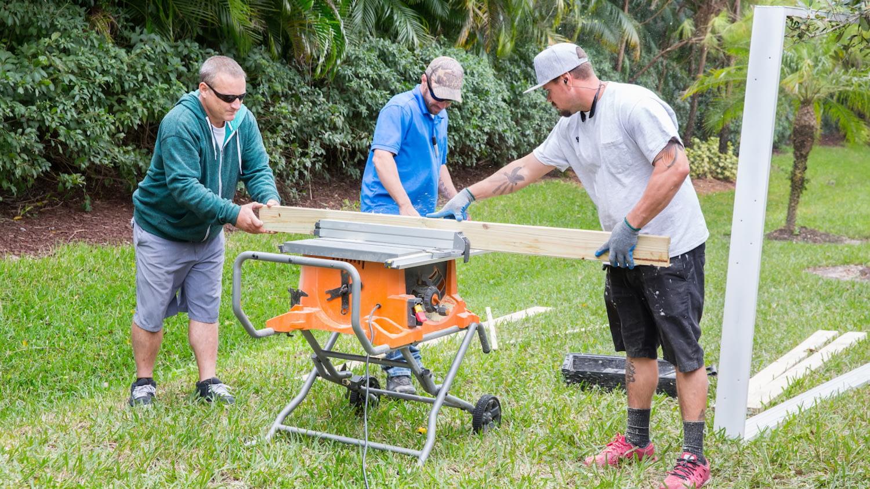 Drei Männer bauen ein Gerüst im Garten und messen dafür ein Brett aus.