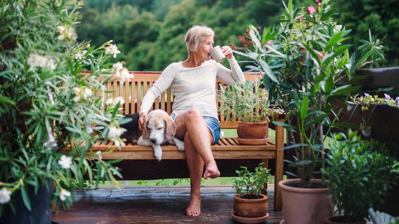 Seniorin sitzt auf der Terrasse auf einer Gartenbank und trinkt einen Kaffee, neben ihr auf der Bank sitzt ein Hund