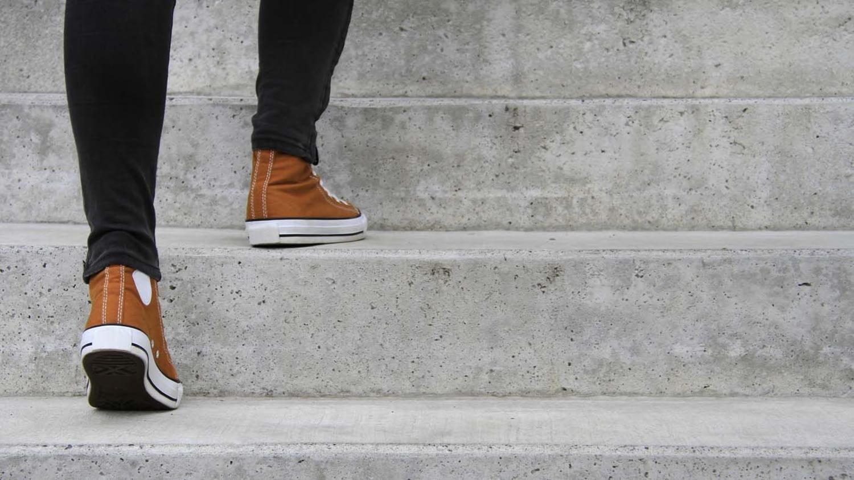 Detailaufnahme einer Person in Sneakern und schwarzer Hose, die Treppenstufen hinaufsteigt