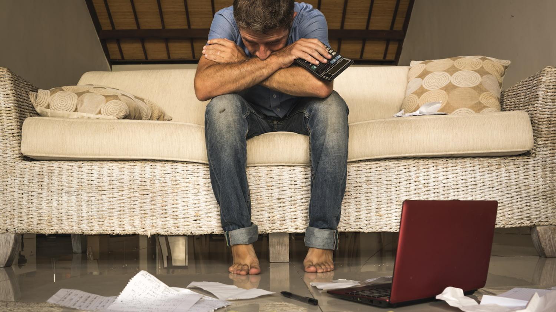 Mann sitzt auf dem Sofa und blickt verzweifelt auf diverse Papiere sowie Laptop und Taschenrechner, die vor ihm auf dem Boden liegen.