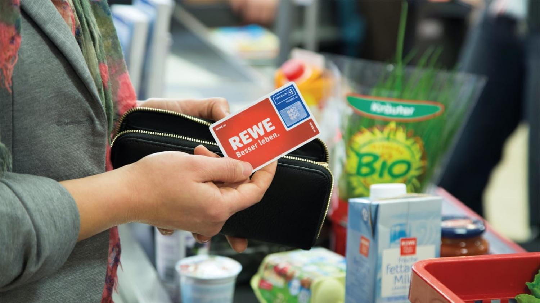 Eine Kundin hält an einer Supermarktkasse eine Paybackkarte von Rewe bereit