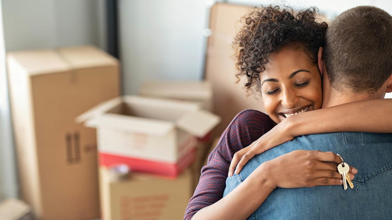 Vor Umzugskartons umarmt eine junge Frau ihren Mann in ihrer neuen Wohnung