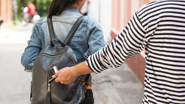 Diebstahlversicherung: Einer jungen Frau wird das Handy aus dem Cityrucksack gestohlen, den sie auf dem Rücken trägt