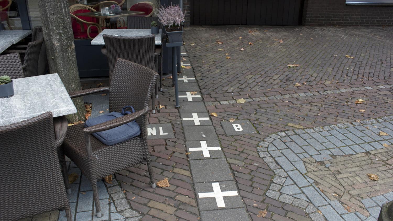 Grenzmarkierungen auf einem Platz vor einem Café in Baarle